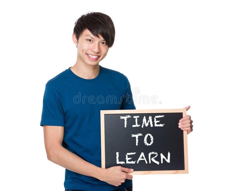 Homme asiatique avec le tableau noir montrant l'expression de l'heure d'apprendre photographie stock