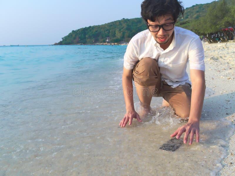 Homme asiatique choqué laissant tomber le téléphone intelligent mobile sur la plage sablonneuse tropicale de la mer Concept d'acc images stock