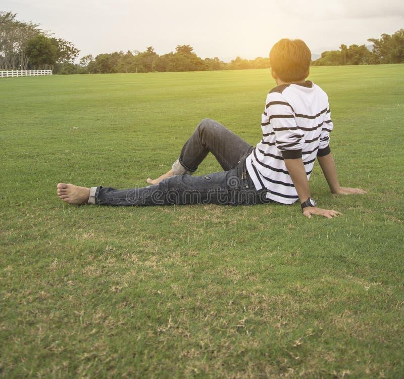 Homme asiatique détendant sur l'herbe appréciant dans un jour en parc avec le fond de ciel, Thaïlande photographie stock libre de droits