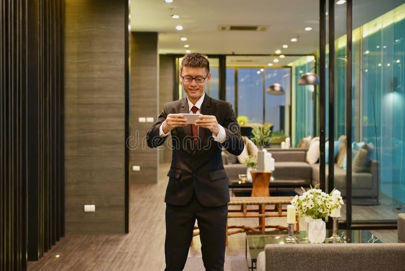 Homme asiatique d'affaires à l'aide d'un smartphone dans le salon de luxe en m photos stock