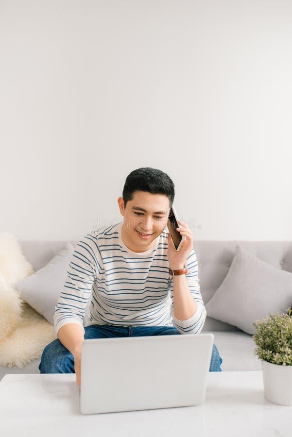 Homme asiatique d'affaires parlant à un téléphone portable et travaillant sur son ordinateur portable photo stock