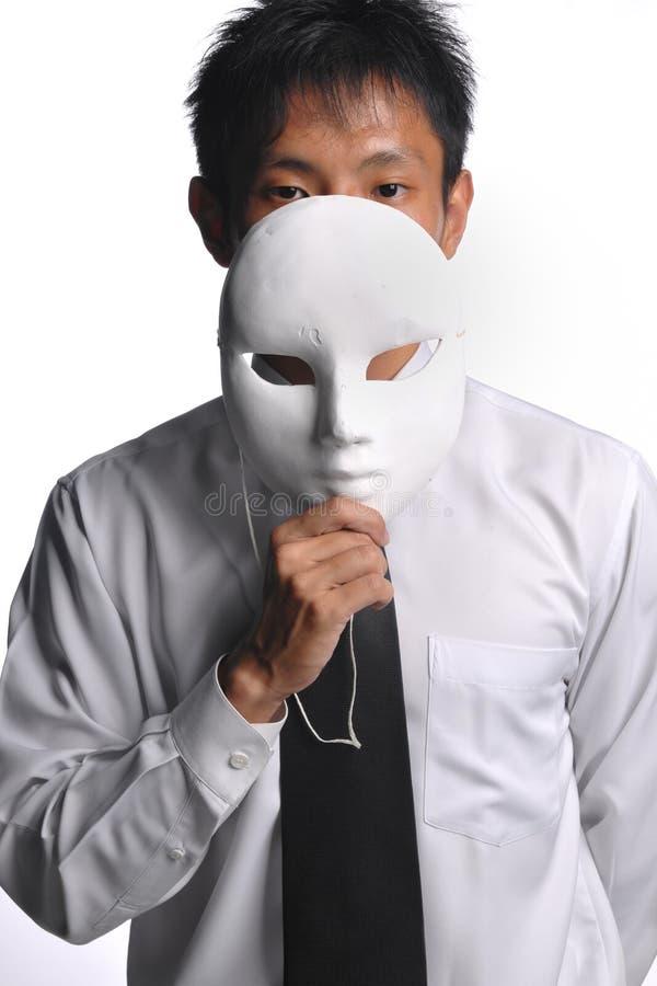 Homme asiatique d'affaires se cachant derrière le masque image stock