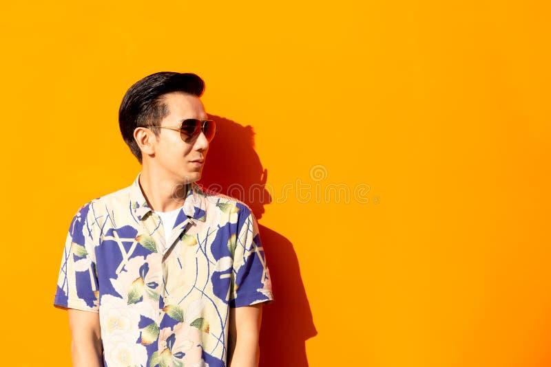Homme asiatique de mode avec des lunettes de soleil sur le fond coloré images libres de droits