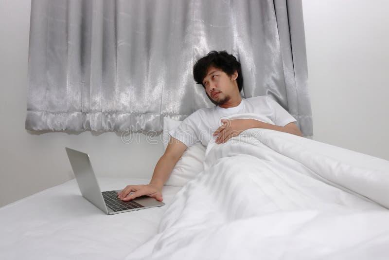 Homme asiatique de paresse fatiguée travaillant sur l'ordinateur portable sur le lit dans la chambre à coucher image stock