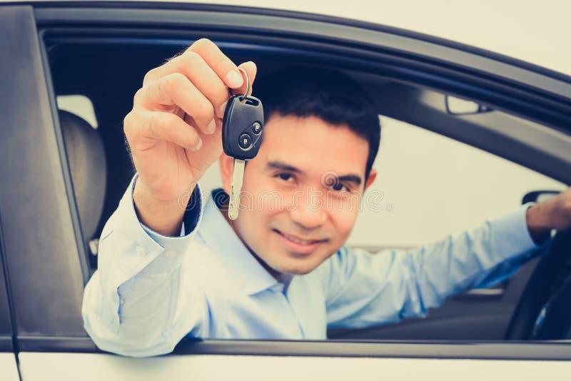 Homme asiatique de sourire comme conducteur montrant la clé de voiture (clé focalisée) images stock