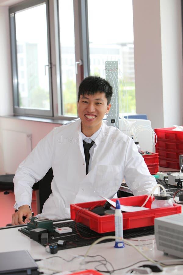 Homme asiatique de sourire travaillant dans un laboratoire images stock