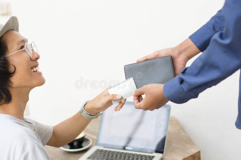 Homme asiatique donnant la carte de banque au bulletin de paie avec l'ordinateur portable et la copie comme fond photos stock