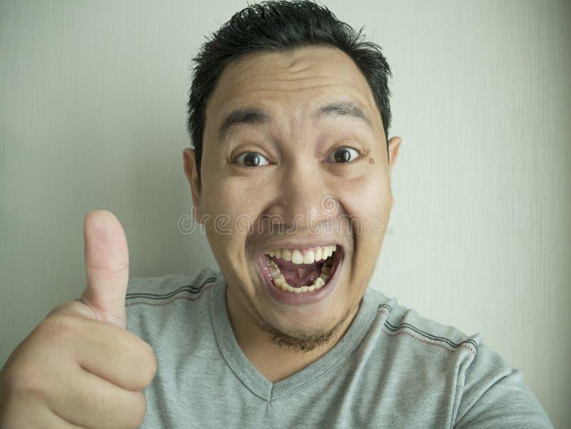 Homme asiatique drôle heureux riant de la caméra image stock