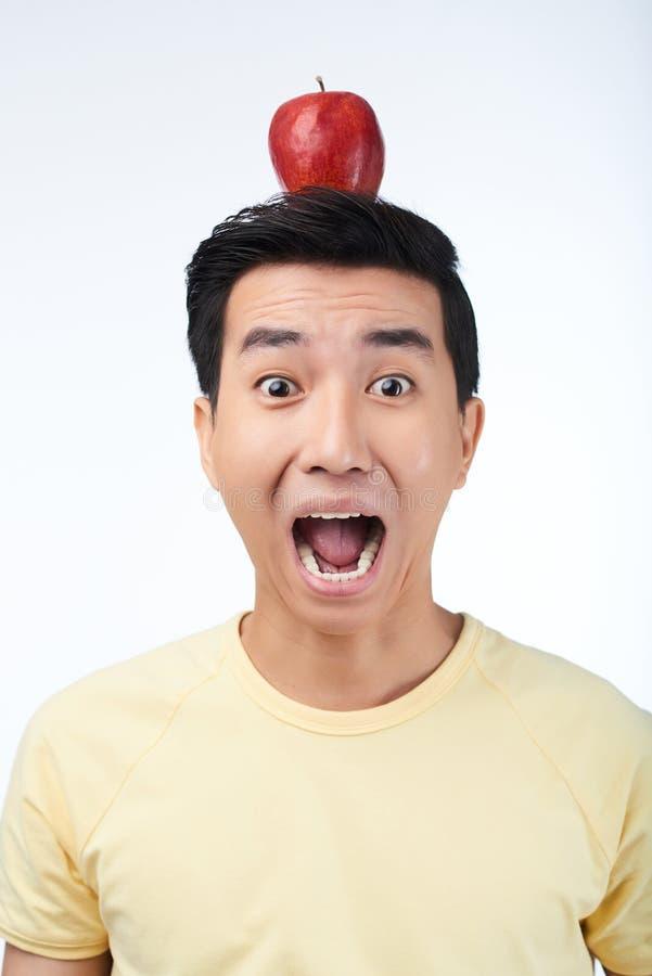 Homme asiatique effrayé avec Apple rouge photo stock