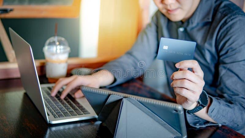 Homme asiatique employant la carte de crédit pour des achats en ligne image stock