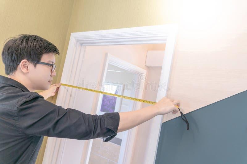 Homme asiatique employant le ruban métrique sur le cadre de porte image stock