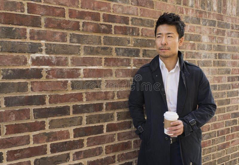 Homme asiatique en passant habillé se tenant avec du café photographie stock libre de droits
