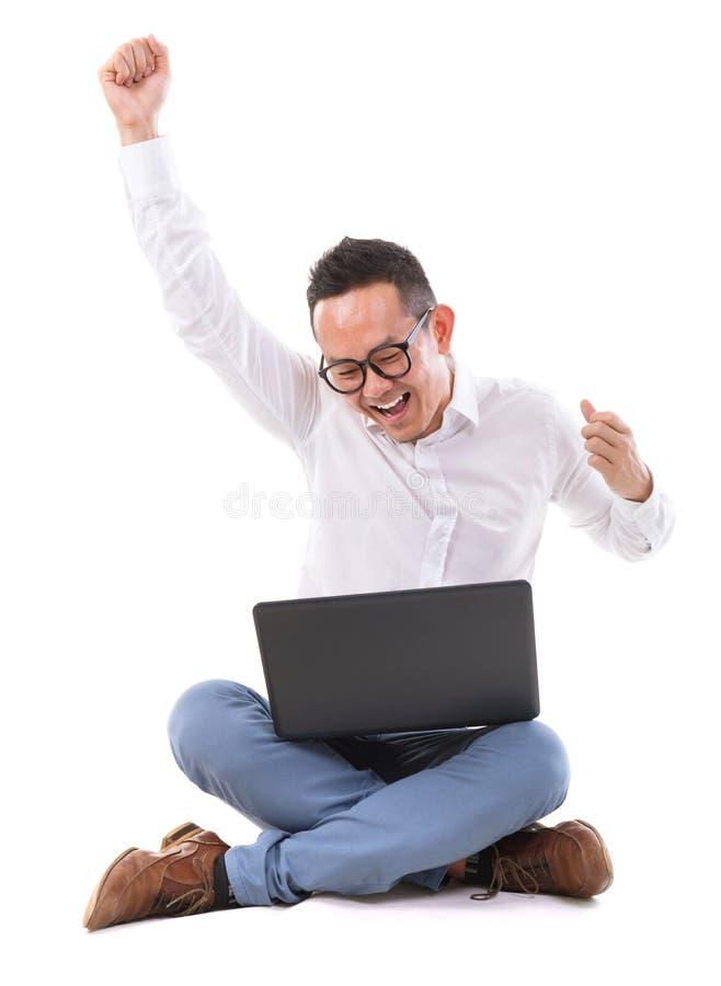 Homme asiatique enthousiaste à l'aide de l'ordinateur portable photographie stock