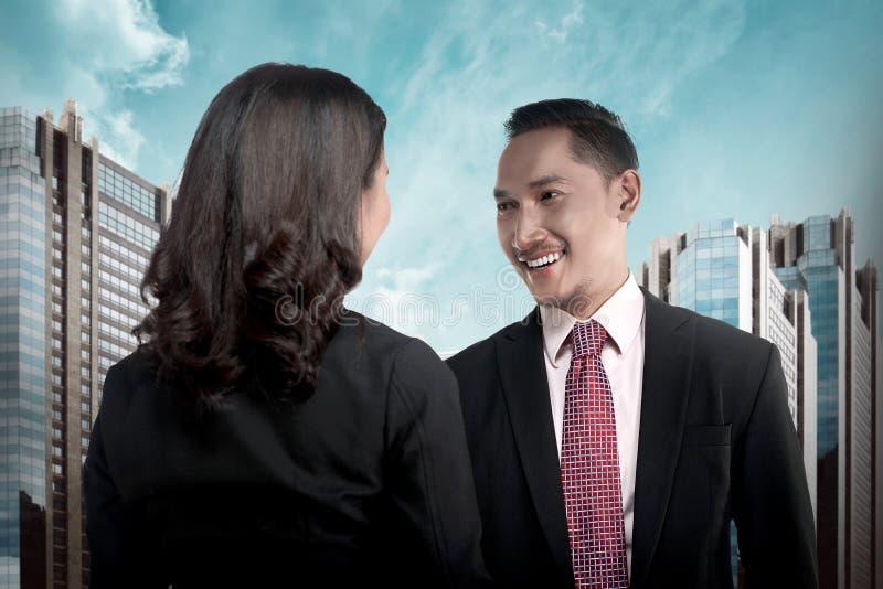 Homme asiatique et femme d'affaires serrant la main photo stock