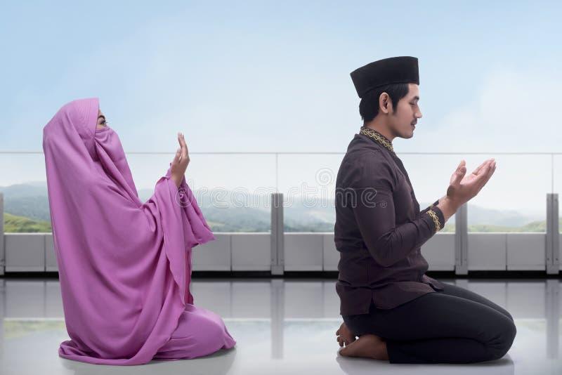 Homme asiatique et femme musulmans priant ensemble image libre de droits