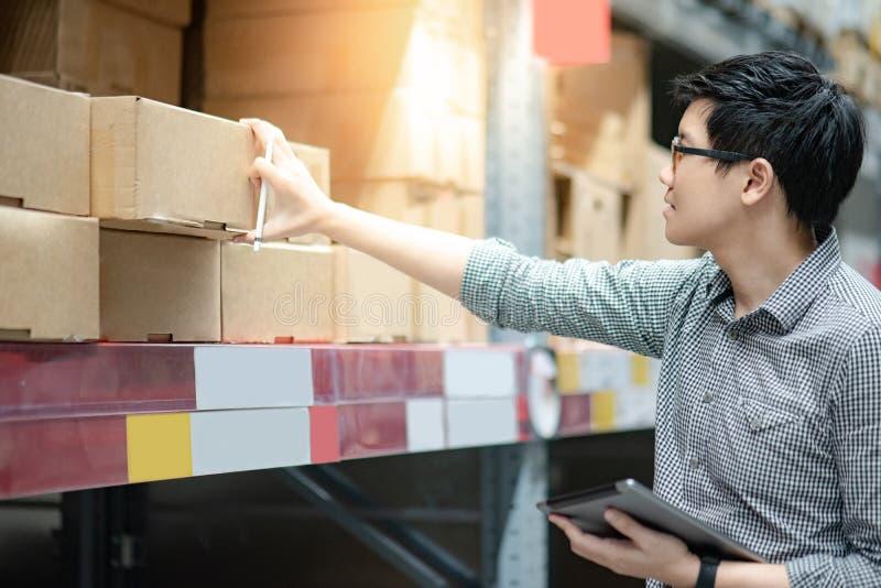 Homme asiatique faisant l'inventaire à l'aide du comprimé dans l'entrepôt image libre de droits