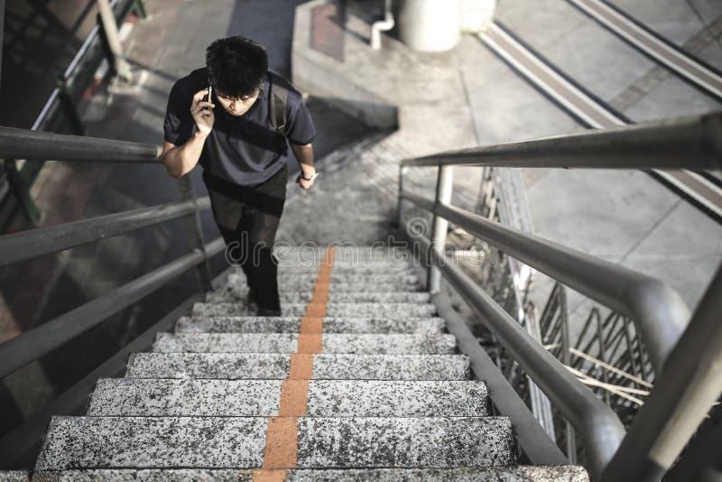 Homme asiatique marchant vers le haut des escaliers dans la ville parlant au téléphone portable. photographie stock libre de droits