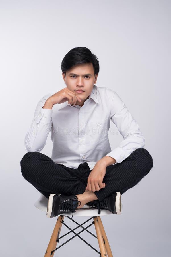 Homme asiatique occasionnel futé assis sur la chaise, posant tout en regardant photographie stock libre de droits