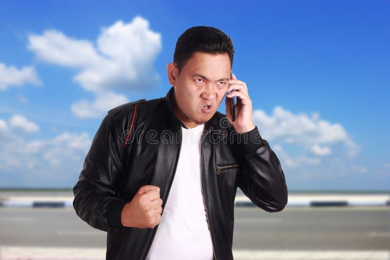 Homme asiatique parlant au téléphone, expression fâchée images libres de droits