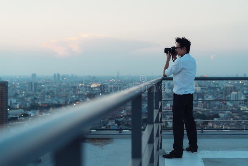 Homme asiatique prenant la photo de paysage urbain sur le dessus de toit de bâtiment dans la situation de faible luminosité Photo image stock