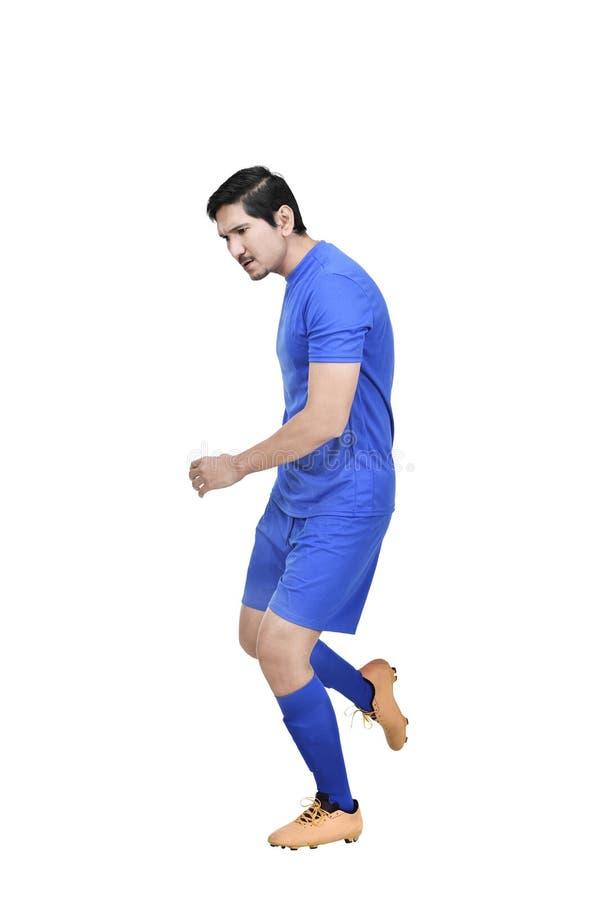 Homme asiatique professionnel de footballer donnant un coup de pied la boule photo stock
