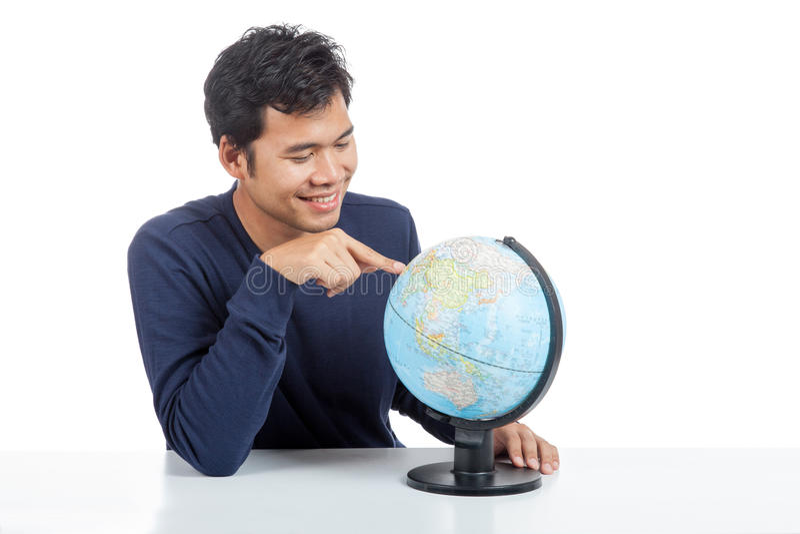 Homme asiatique recherchant sur un globe du monde image stock