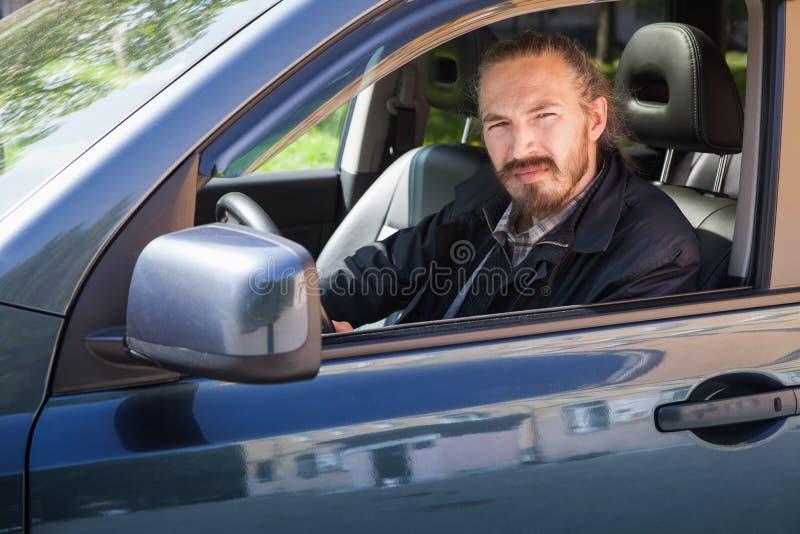 Homme asiatique sérieux barbu avec des clés comme conducteur de voiture images stock