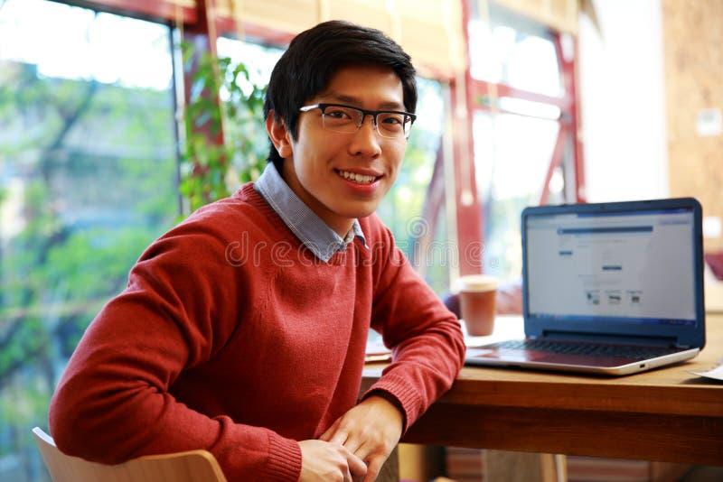 Homme asiatique s'asseyant à la table avec l'ordinateur portable photos libres de droits