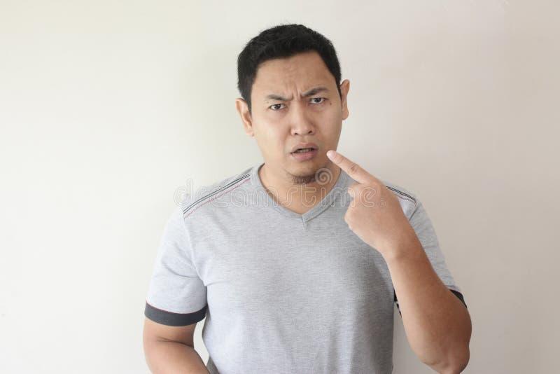 Homme asiatique se dirigeant avec l'expression malheureuse image libre de droits