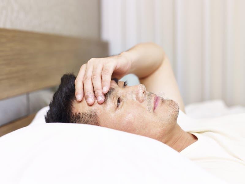 Homme asiatique se trouvant sur la main de lit sur le front image libre de droits
