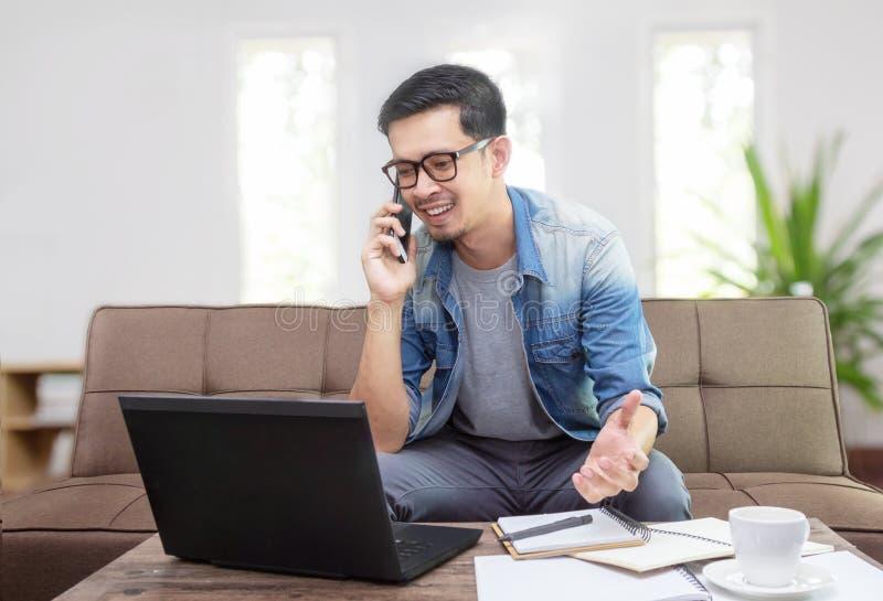 Homme asiatique souriant et employant des affaires parlantes de smartphone photos stock