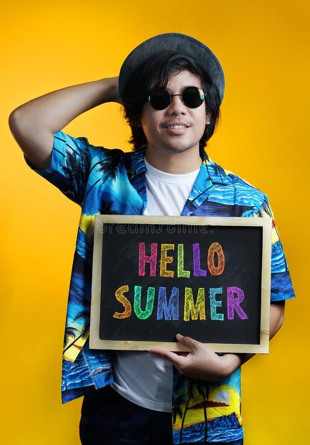 Homme asiatique stockant le texte coloré d'été de bonjour sur le tableau noir Weari photos libres de droits