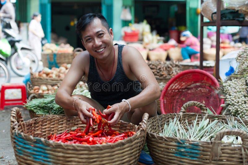 Homme asiatique sur frais rouge de vente de sourire de marché en plein air photographie stock
