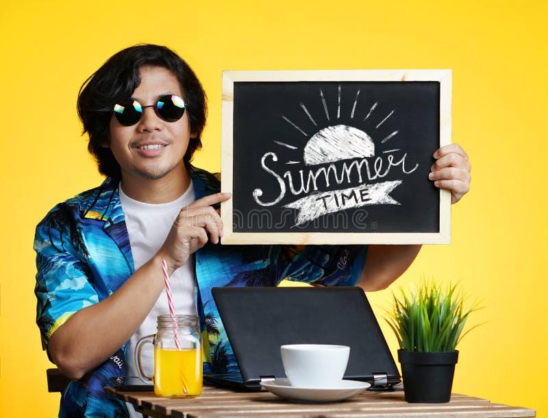 Homme asiatique tenant la typographie d'heure d'été sur le tableau noir tandis que Wor photo stock