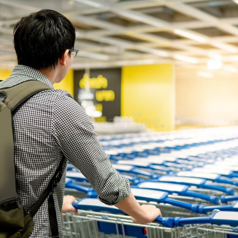 Homme asiatique tirant le caddie dans le supermarch? photographie stock libre de droits