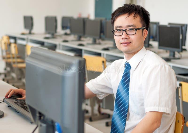 Homme asiatique travaillant dans la salle des ordinateurs photos libres de droits