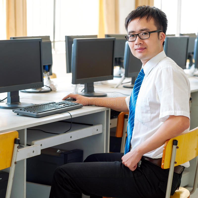 Homme asiatique travaillant dans la salle des ordinateurs photographie stock libre de droits