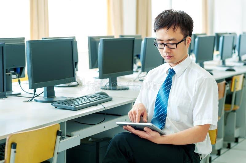 Homme asiatique travaillant dans la salle des ordinateurs image stock