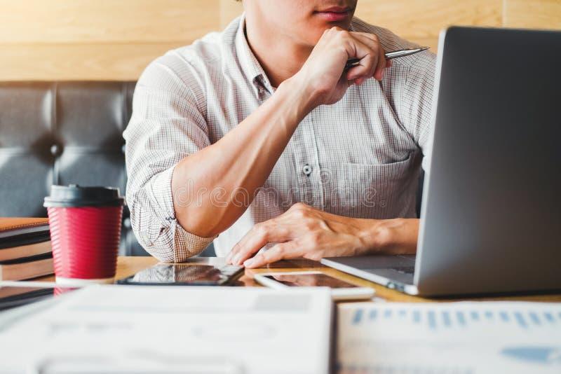 Homme asiatique utilisant l'ordinateur portable travaillant sur sa nouvelle id?e de projet dans le fonctionnement de caf? images stock