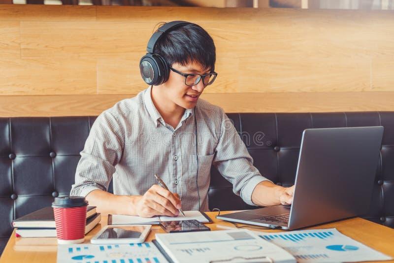 Homme asiatique utilisant l'ordinateur portable travaillant sur sa nouvelle id?e de projet dans le fonctionnement de caf? images libres de droits