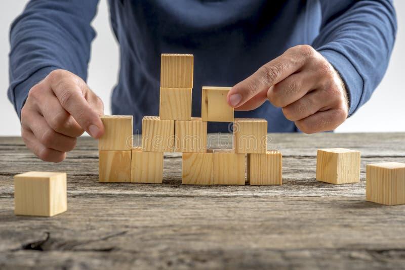 Homme assemblant les cubes en bois sur le Tableau images libres de droits