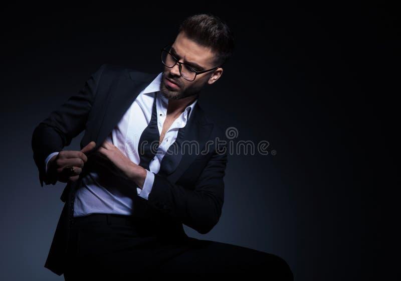 Homme assis dans le smoking recherchant dans le sien la poche d'intérieur image libre de droits