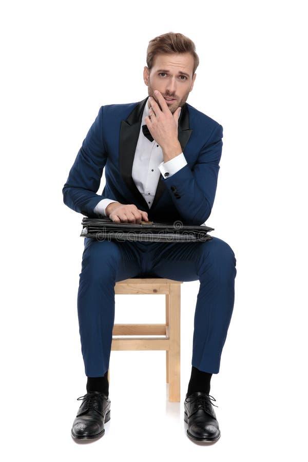 Homme assis de mode pensant tout en tenant la valise noire sur le recouvrement images stock
