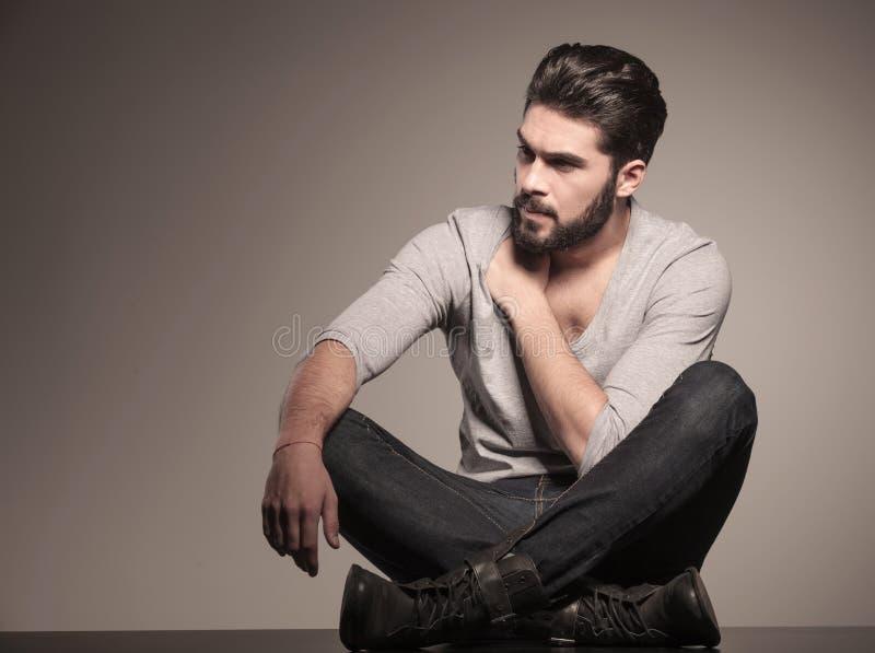 Homme assis de mode regardant à son côté photographie stock
