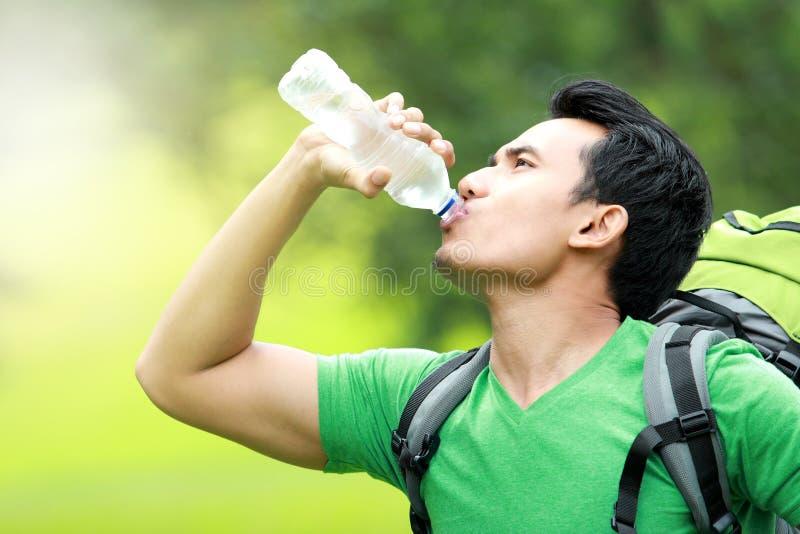 Homme assoiffé buvant une bouteille de l'eau photographie stock libre de droits
