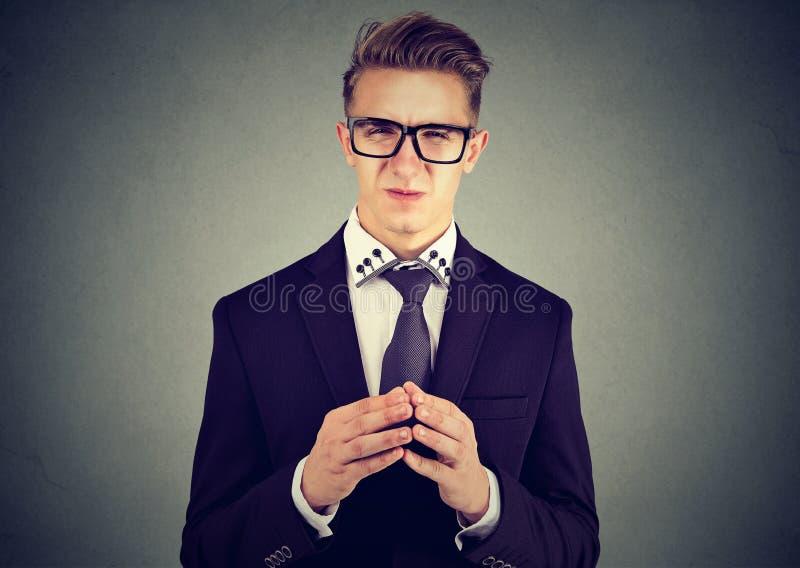 Homme astucieux d'affaires en verres regardant avec dégoût l'appareil-photo photo libre de droits