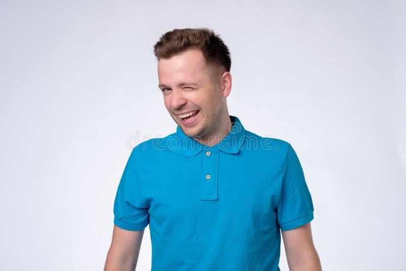 Homme astucieux heureux dans le T-shirt bleu clignant de l'oeil un oeil images libres de droits