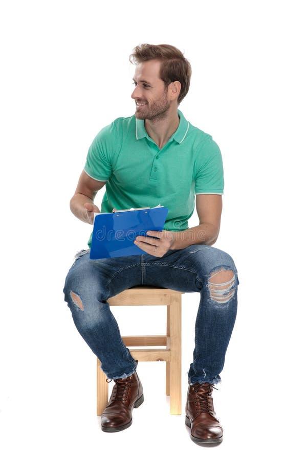 Homme attirant assis dans le polo vert présentant un presse-papiers photos stock