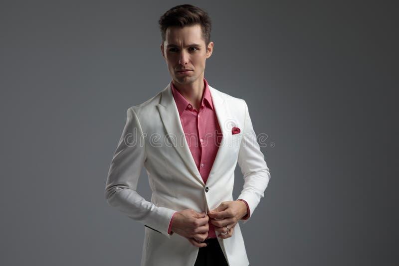 Homme attirant boutonnant sa veste de salon et regardant loin image stock