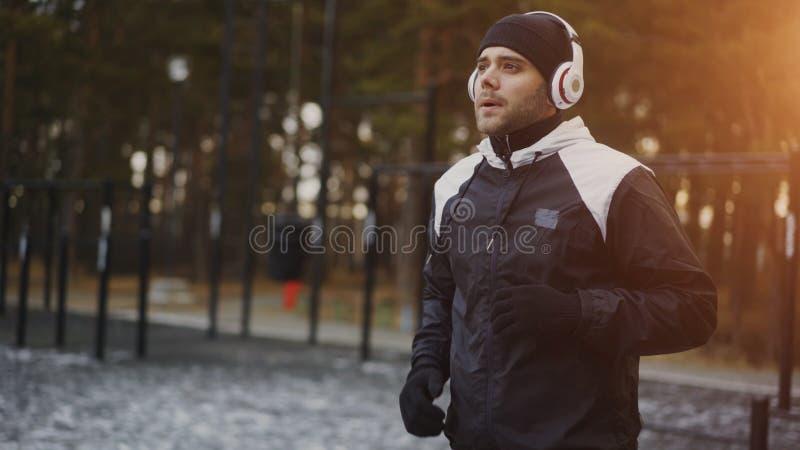 Homme attirant dans des écouteurs faisant l'exercice d'échauffement se préparant à pulser tandis que musique de écoute en parc d' images libres de droits